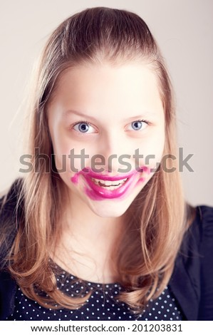 Happy teen girl making funny faces with pomade on lips and cheeks - stock photo