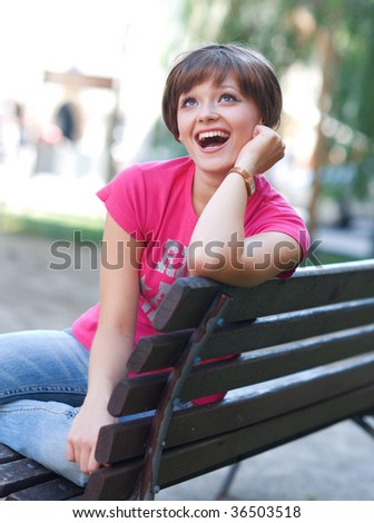 happy teen girl on the park bench - stock photo