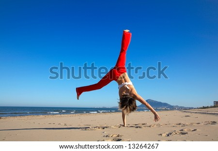 happy teen girl playing/doing gymnastics on the beach