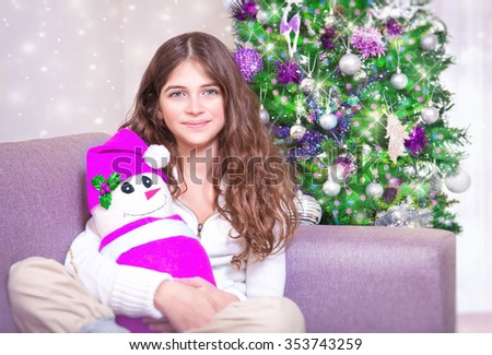 Happy teen girl sitting near Christmas tree with snowman soft toy, enjoying gift, spending winter holidays at home - stock photo