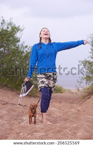 Happy teen girl standing on the beach with her dog and enjoy the rain - stock photo