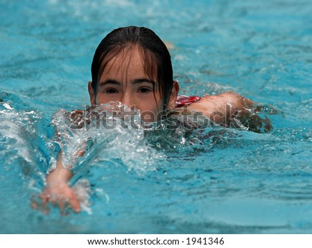 Happy teen girl swimming in the pool
