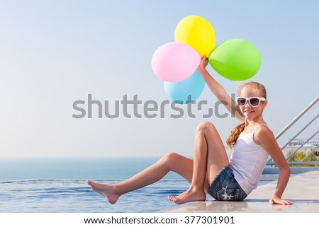 happy teen girl with balloons sitting near a swimming pool at the day time. - stock photo
