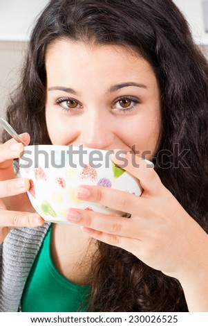 Happy teen girl with beautiful brown eyes drinking from a bowl maybe milk or soup - stock photo