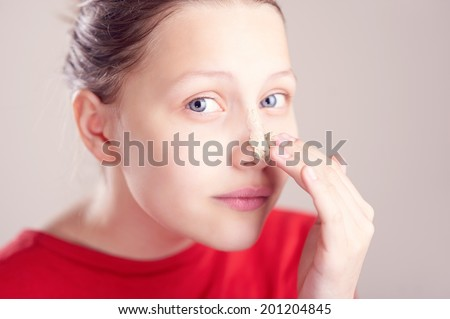 Happy teen girl with scrub mack on her face having fun and making funny faces
