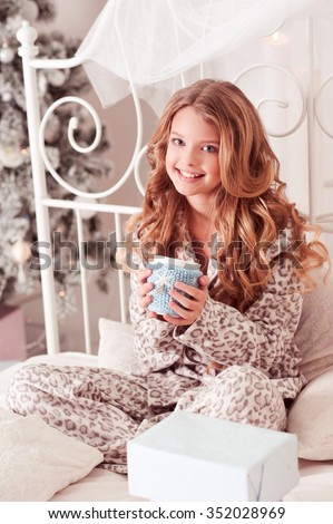 Happy teen girl 8-10 year old sitting in bed with cup of tea in room. Christmas tree. Looking at camera. Happiness. Celebration.  - stock photo