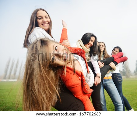 Happy teen girls having good fun time outdoors holding friend in arms up - stock photo