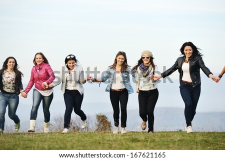 Happy teen girls having good fun time outdoors running and jumping - stock photo