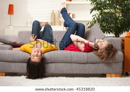 Happy teen girls resting on sofa at home, smiling. - stock photo