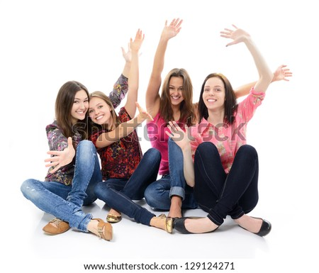 happy teen girls sitting together and smiling with hand up over white - stock photo