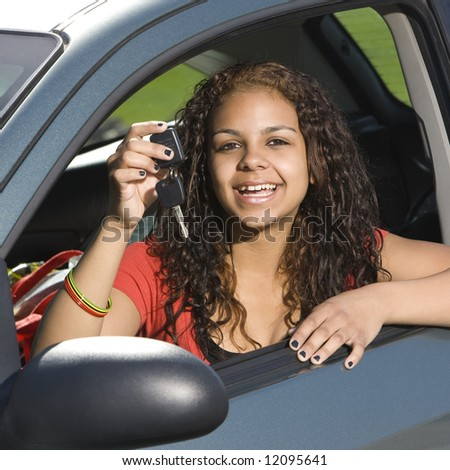 Happy teen holds up car keys and smiles - stock photo