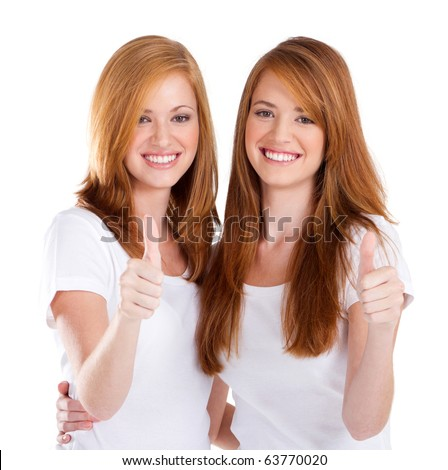happy teen sisters giving thumbs up