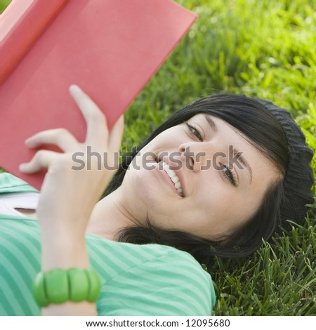 Happy teen studies with book in the grass - stock photo