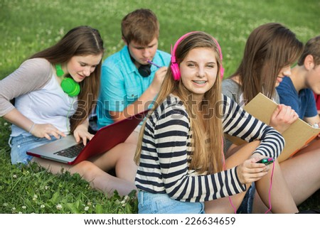 Happy teen with male and female friends outdoors - stock photo