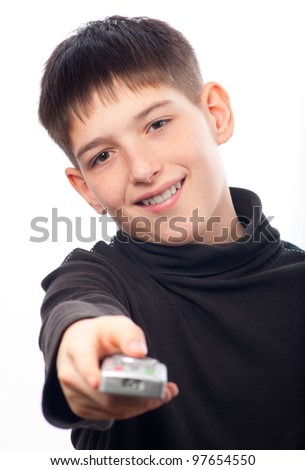 Happy teenage boy changing channels on television with remote control isolated on white.