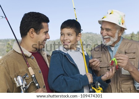 Happy teenage boy fishing with father and grandfather - stock photo