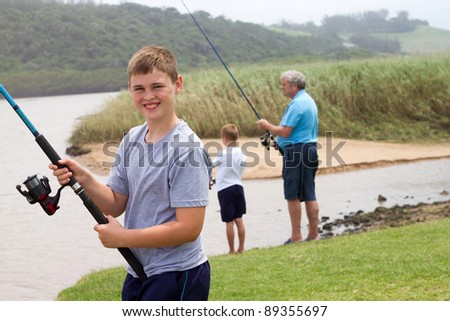 happy teenage boy fishing with grandpa and little brother