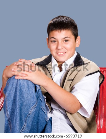 Happy teenage boy in a relaxed pose in a red chair - stock photo