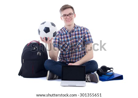 happy teenage boy sitting with laptop, backpack and soccer ball isolated on white background