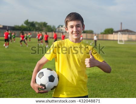 happy teenage boy with a soccer ball in his hand against the background of the stadium. Training - stock photo