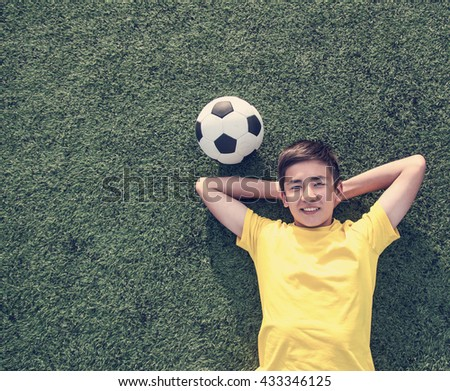 happy teenage boy with a soccer ball lying on the green lawn. Shot from top.