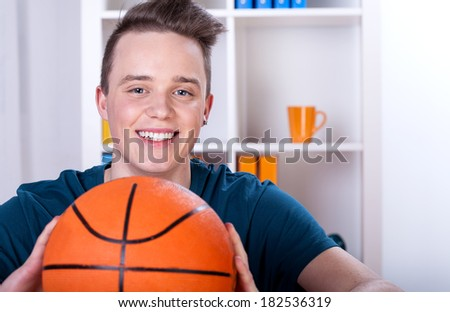 Happy teenage boy with ball to the basket - stock photo
