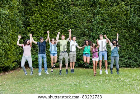 Happy Teenage College Students Jumping at Park - stock photo