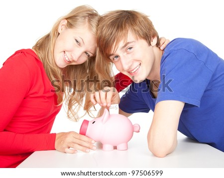 happy teenage couple putting money to piggy bank - stock photo