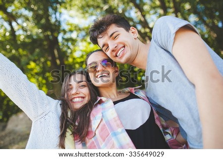 Happy teenage friends smiling outdoors on nature. Handsome young people having fun together and posing for camera. - stock photo