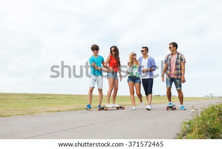 happy teenage friends with longboards outdoors