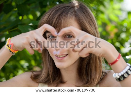 Happy teenage girl forming heart with her hands - stock photo