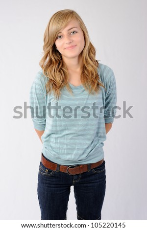 Happy Teenage Girl. Happy thirteen year old girl standing with her hands behind her back. Note: Not Isolated. - stock photo