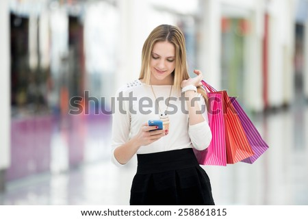 Happy teenage girl holding bags with purchases, smiling while looking at phone in shopping center. Received good news, reading message, texting, dialing number, using app on smartphone - stock photo