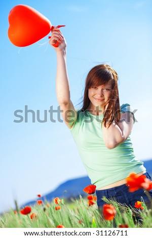 Happy teenage girl holding balloon heart in poppy field - stock photo