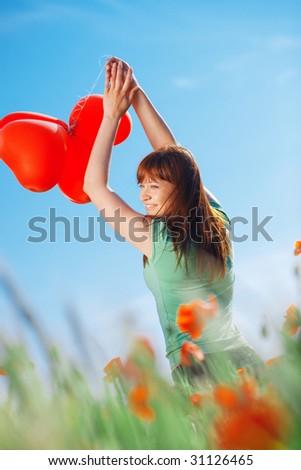 Happy teenage girl holding balloons hearts - stock photo