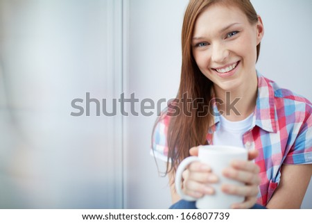 Happy teenage girl holding mug and looking at camera with smile - stock photo