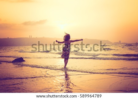 happy teenage girl jumping at the beach, rear view, sunset shot