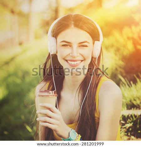 Happy teenage girl listening to music on headphones in park in summer. Closeup of attractive young Caucasian woman with white headphones and takeaway coffee outdoors in park. Vibrant, retouched. - stock photo