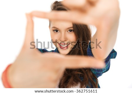 happy teenage girl making frame of fingers - stock photo