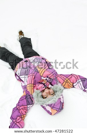 Happy teenage girl making snow angel in winter - stock photo