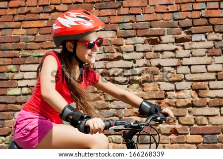 happy teenage girl on a bicycle on brick wall background - stock photo