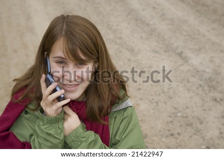 Happy teenage girl on a gravel  road, talking on her cell phone - stock photo