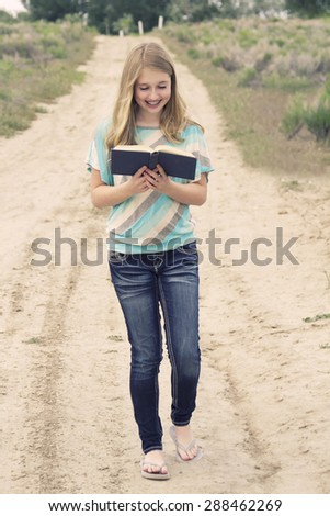 Happy teenage girl reading a book while walking down a dirt road in rural area, with an instagram or vintage filter