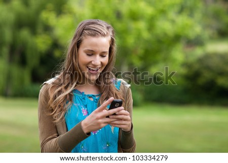 Happy teenage girl receiving a text on her mobile phone while standing in a park - stock photo