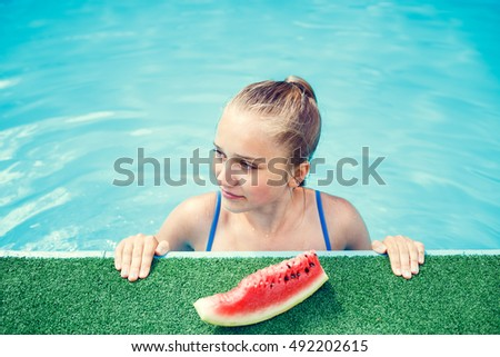Happy teenage girl relaxing in swimming pool in summer holidays