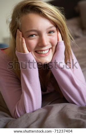 Happy Teenage Girl Sitting In Bedroom - stock photo