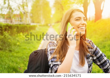 Happy teenage girl talking on the phone outdoors laughing. Cute young female student speaking on the phone in park on sunny summer day. - stock photo