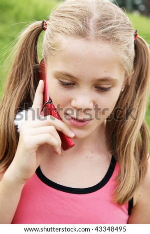 Happy teenage girl talks on cellural phone on green grass background - stock photo