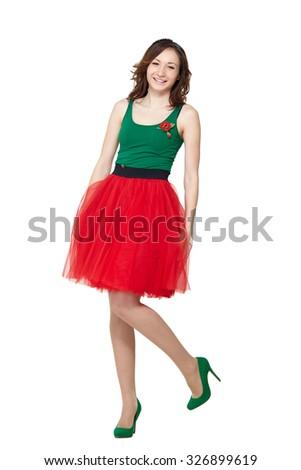 Happy teenage girl wearing summer skirt standing on white background. Smiling pretty brunette lady model posing in studio - stock photo