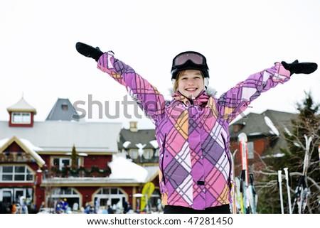 Happy teenage girl with arms raised in ski helmet at winter resort - stock photo